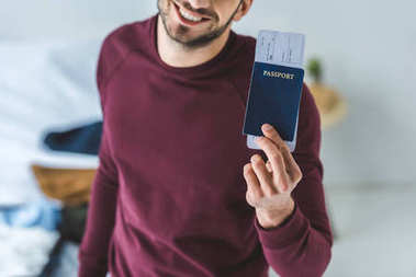 Cropped view of smiling man holding passport and air ticket stock vector