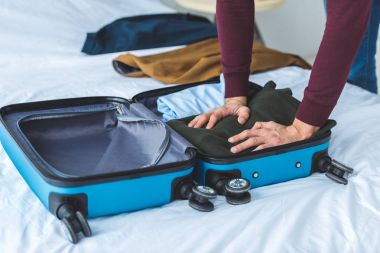 cropped view of man packing clothes into travel bag