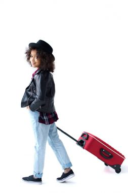 side view of stylish little child walking with luggage isolated on white