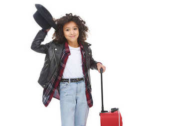 happy little child in stylish clothing and hat with luggage isolated on white