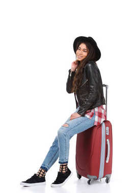 stylish young woman sitting on luggage isolated on white