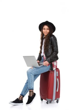 Stylish young woman using laptop while sitting on luggage isolated on white stock vector