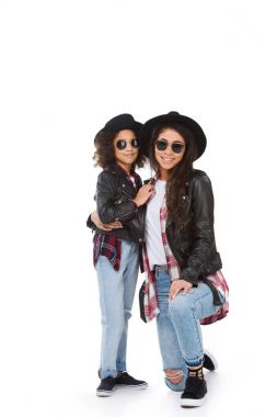 stylish mother and daughter in hats and sunglasses looking at camera isolated on white