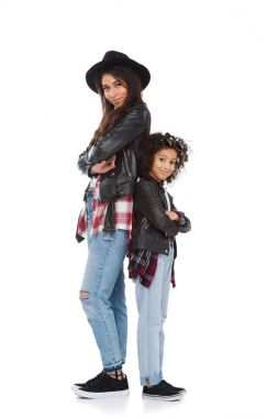 happy mother and daughter in similar clothes standing back to back isolated on white