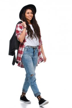 beautiful walking young woman in stylish plaid shirt and leather jacket isolated on white