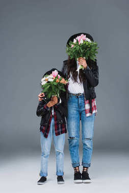 mother and daughter covering faces with bouquets on grey
