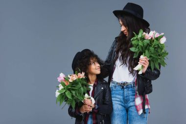 beautiful mother and daughter with beautiful bouquets isolated on grey