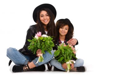 mother and daughter sitting on floor with beautiful bouquets isolated on white