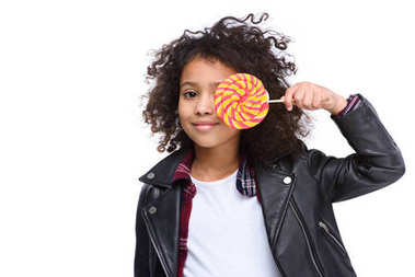 beautiful little child covering eye with lollipop isolated on white
