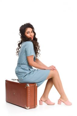 Attractive young woman sitting on vintage suitcase isolated on white stock vector