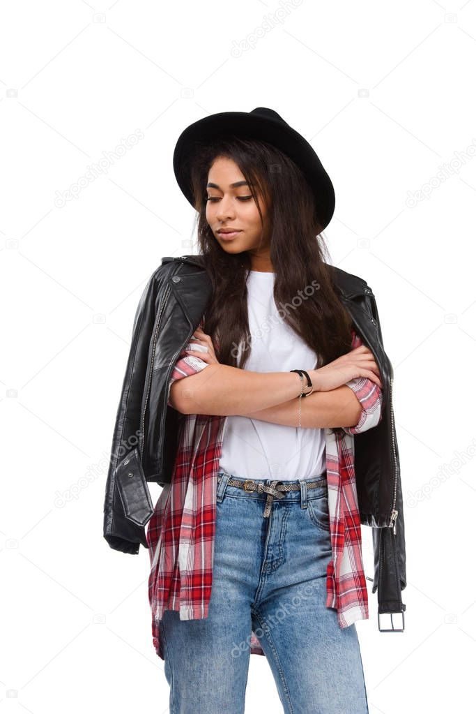 young woman in stylish clothing and hat with crossed arms isolated on white
