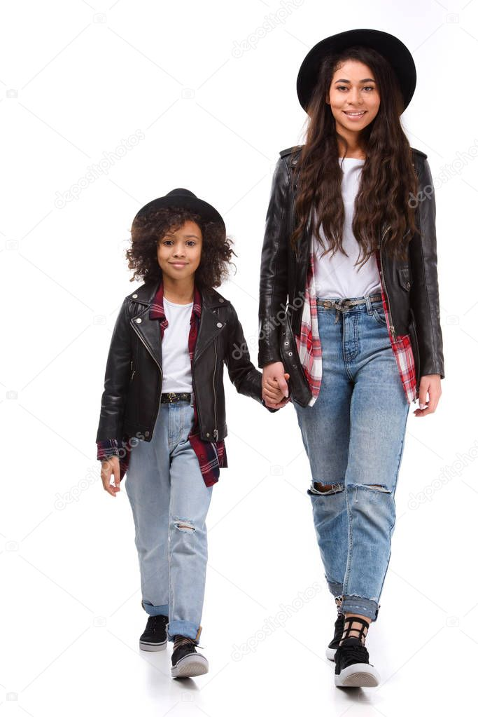 stylish mother and daughter walking together and holding hands isolated on white