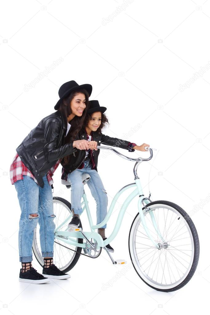 mother teaching her daughter daughter to ride bicycle isolated on white