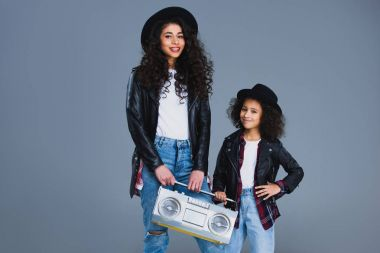 Mother and daughter with retro boombox isolated on grey stock vector