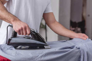 cropped image of man ironing shirt on ironing board in living room