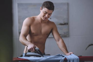 sexy shirtless man ironing shirt on ironing board
