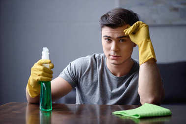 handsome man with spray bottle and rubber gloves looking at camera