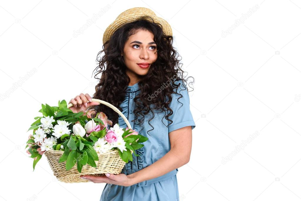 attractive young woman in dress and boater hat with basket of flowers isolated on white