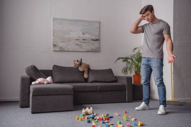 man standing and looking at children toys scattered on floor