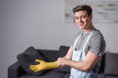 smiling handsome man wearing rubber glove for cleaning in living room