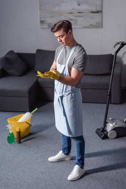 handsome man wearing rubber gloves for cleaning in living room