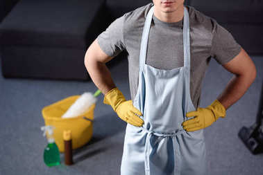 cropped image of man standing in apron in living room