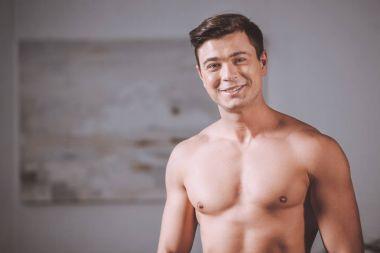 smiling seductive naked man looking at camera