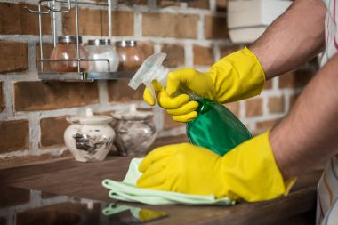 cropped image of man cleaning kitchen with spray bottle and rag