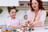 Fotografie Babička a malou vnučkou jíst lahodný dortík s ovocem v kuchyni