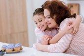 Fotografie Babička a malá vnučka, při pohledu na krémové košíčky