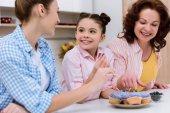 Fotografie tři generace žen zdobení cupcakes s borůvky spolu v kuchyni