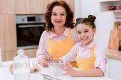 Fotografie glückliche Großmutter mit kleinen Enkelin zusammen zu kochen und Blick in die Kamera
