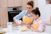 Fotografie krásná mladá matka a dcera nalévání mléka do mísy na těsto v kuchyni