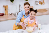 Fotografie mother and daughter mixing dough for pastry at kitchen