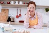 schöne Reife Frau sprechen per Telefon beim Kochen in der Küche