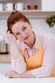 Close-up Portrait schöne Reife Frau mit Schürze in Küche und Blick in die Kamera