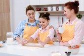Fotografie drei Generationen von glücklichen Frauen Rollen Teig für Kekse zusammen in Küche