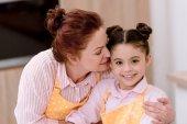 Großmutter umarmt kleine Enkelin beim Kochen in Schürzen