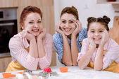 Fotografie drei Generationen von Frauen in Schürzen mit Mehl auf Flächen in Küche und Blick in die Kamera