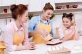 Fényképek három generáció, nők özönlenek a tésztát sütés Cupcakes konyha formák együtt