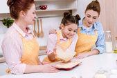 Fényképek három generáció a szép nők özönlenek a tésztát sütés Cupcakes konyha formák