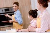 Fényképek három generáció a gyönyörű nők együtt a konyha tészta sütés kötények