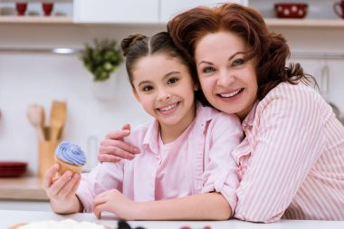 grandmother and little granddaughter with cupcake sitting at kitchen and looking at camera