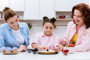three generations of happy women decorating dessert with berries together at kitchen