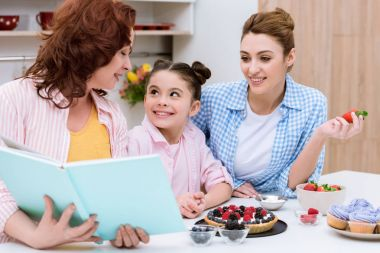 three generations of women reading recipe book together at kitchen
