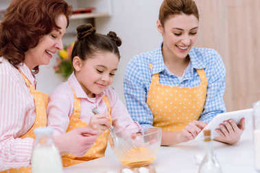 Three generations of happy women in aprons preparing dough together at kitchen stock vector