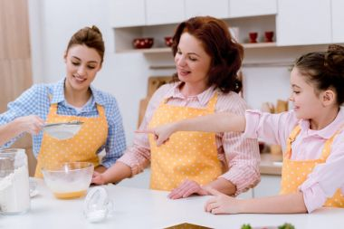 three generations of happy women preparing dough together at kitchen