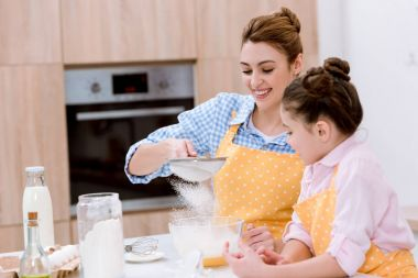 smiling young mother and daughter with sieve preparing dough for pastry together