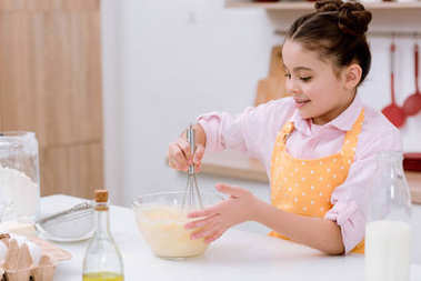 adorable little child mixing dough for pastry