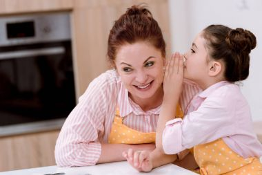 grandmother gossiping with little granddaughter while cooking